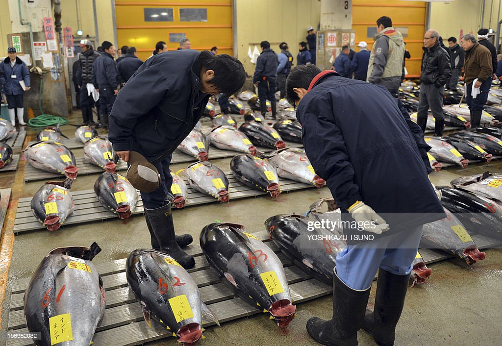 Fishmongers bow before the first trading of bluefin tuna of the new year at Tokyo's Tsukiji fish market on January 5, 2013. A 222kg bluefin tuna was traded at 155.4 million yen (1.77 million USD) at the wholesale market, smashing a previous record. AFP PHOTO / Yoshikazu TSUNO