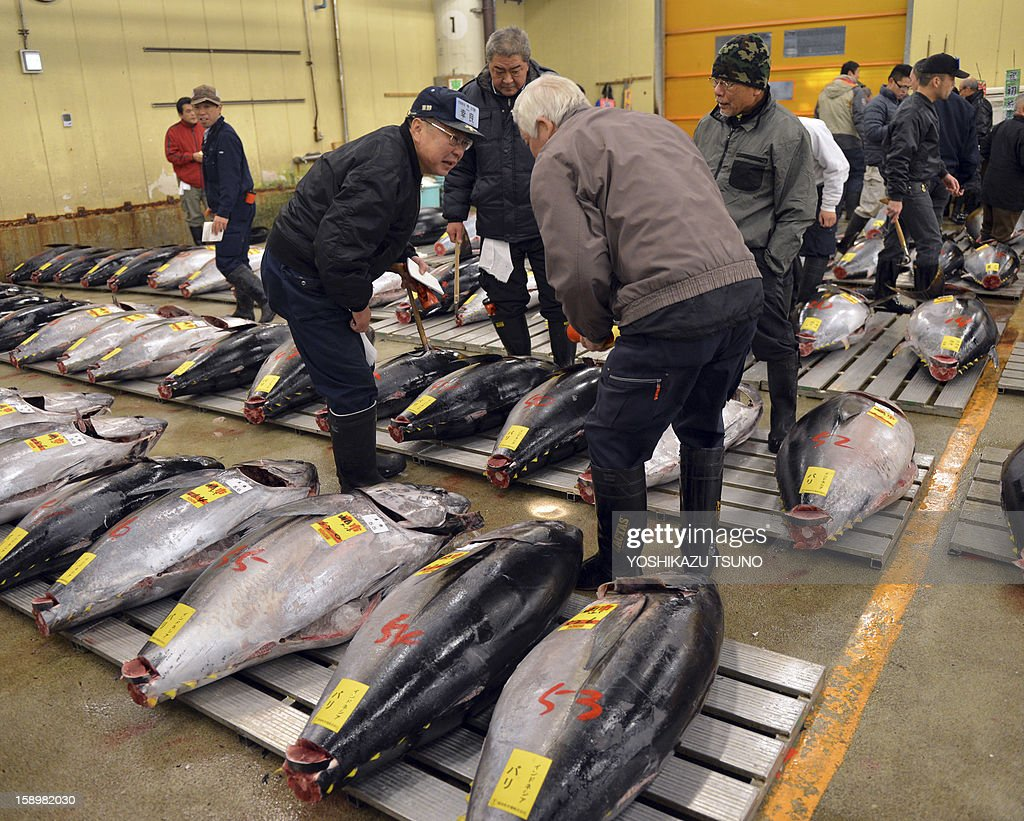 Fishmongers bow before the first trading of the bluefin tuna of the new year at Tokyo's Tsukiji fish market on January 5, 2013. A 222kg bluefin tuna was traded at 155.4 million yen (1.77 million USD) at the wholesale market, smashing a previous record. AFP PHOTO / Yoshikazu TSUNO