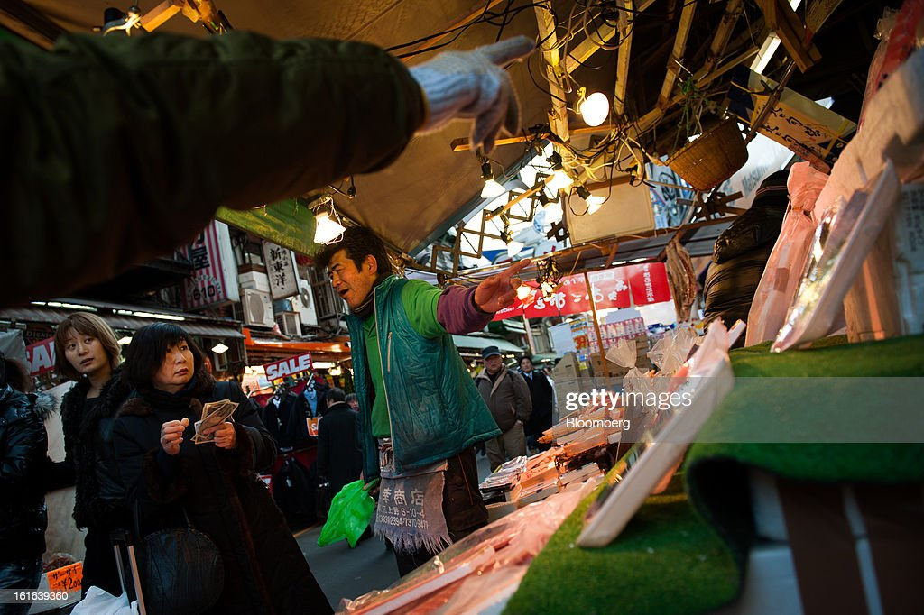 Fishmongers serve a customer at a stall at the Ameya-Yokocho market in Tokyo, Japan, on Wednesday, Feb. 13, 2013. Japan's economy unexpectedly shrank last quarter as falling exports and a business investment slump outweighed improved consumption, highlighting the challenge facing Prime Minister Shinzo Abe as he seeks to end deflation. Photographer: Noriko Hayashi/Bloomberg via Getty Images