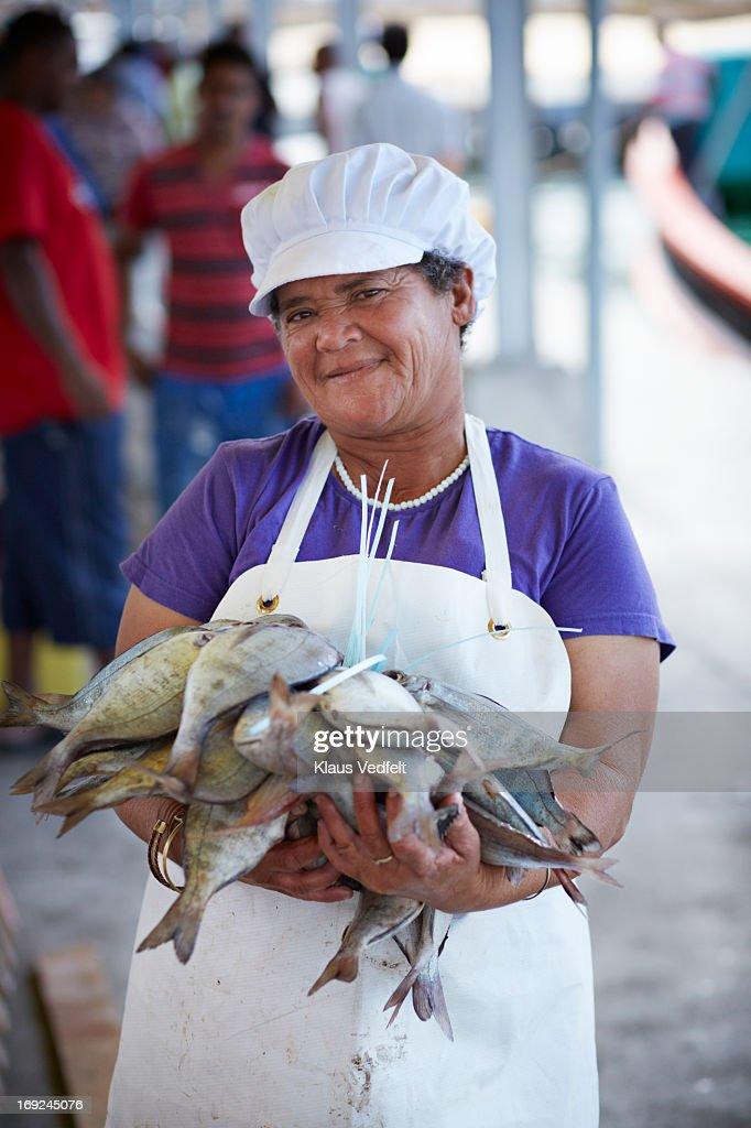 Fishworker holding big stack of fish at market : Stock Photo