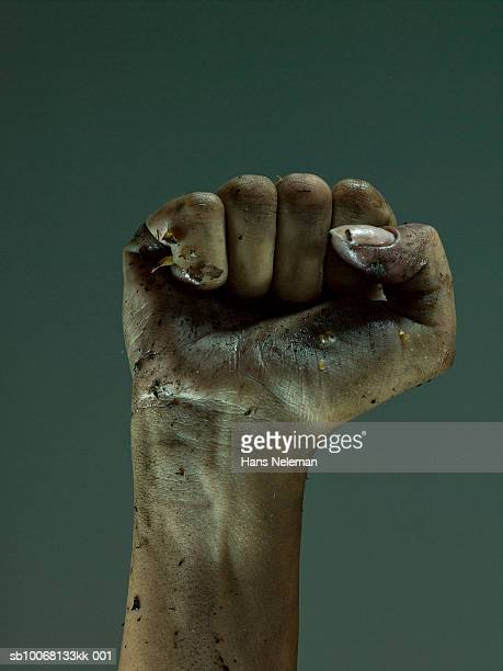 Fist covered with dirt and leaves