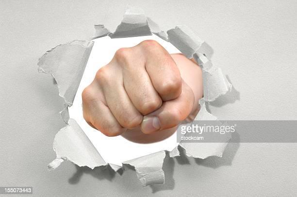 Faust punching durch ein Loch im Papier mit zerrissenen