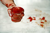Fists with blood. Fighter. Fist blood closeup on the background of the drops of blood on the floor. Fighter fighter shows a bloody hand folded in a fist