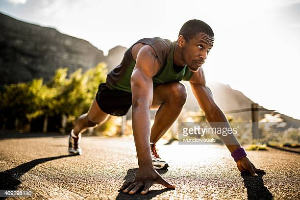 Fit African American athlete in a starting position
