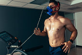 Fit and muscular athlete with mask running on treadmill for monitoring his performance. Sportsman in sports science lab measuring his performance.