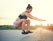 Fit athletic woman exercising in sunset with city in background, wearing pink shorts and top