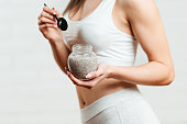 Fit, attractive woman holding a glass jar of chia pudding