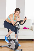 Fit brunette working out on exercise bike at home in the living room