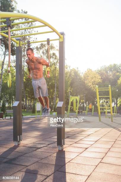 Fit caucasian man strengthening his muscles holding on rings
