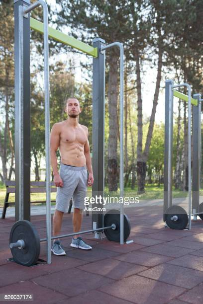 Fit caucasian man training with dumbbells outdoor in the park