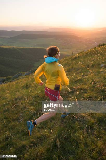 Fit caucasian woman trail running outdoor on green meadow