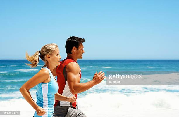 Fit couple jogging by the sea