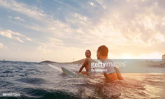 Fit couple surfing at sunset - Surfers friends having fun inside ocean - Extreme sport and vacation concept - Focus on man head - Original sun color tones : Stock Photo