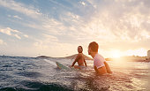 Fit couple surfing at sunset - Surfers friends having fun inside ocean - Extreme sport and vacation concept - Focus on man head - Original sun color tones