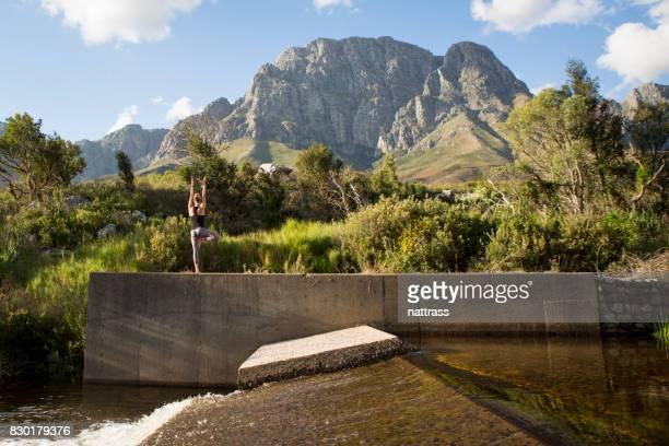Monter la femelle pratiquer l'yoga au bord de la rivière
