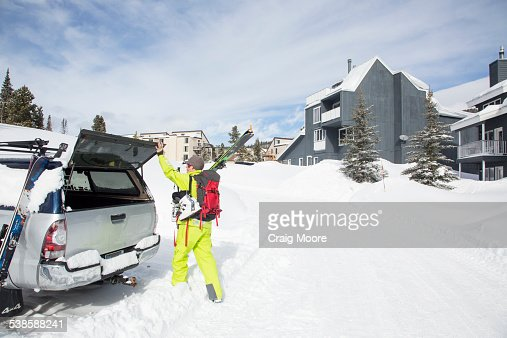 A fit female skier loads her ski gear in a truck at Big Sky Resort in Big Sky, Montana.