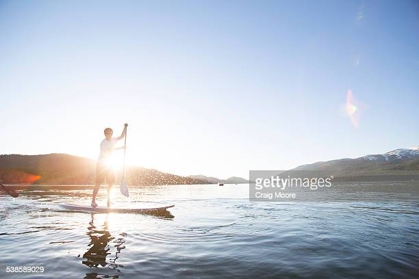 A fit female stand up paddle boards (SUP) at sunset on Whitefish Lake in Whitefish, Montana.