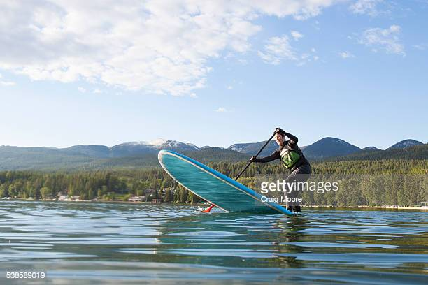 A fit female stand up paddle boards during the spring on Whitefish Lake in Montana.