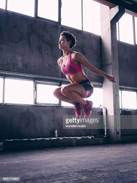 Fit ragazza facendo una forza saltare in aria Librarsi nell'aria