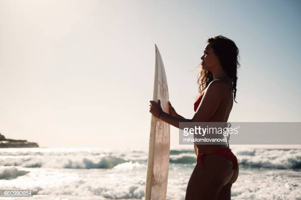 Fit girl posing with surfboard