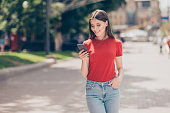 Fit girl smiling and looking into the phone holding her hand in the pocket of blue jeans on a hot summer day