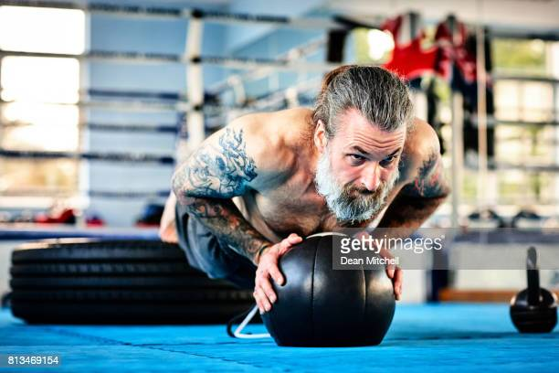 Fit male exercising with medicine ball in the gym