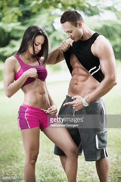 Fit Man and Woman Showing Pack Abs at Outdoor Exercise