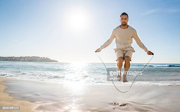 Fit man jumping rope at the beach