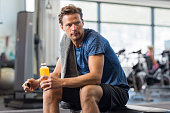 Handsome young man in sportswear holding bottle of fresh orange juice while resting at gym.Thoughtful fit man sitting alone holding a bottle of energy drink. Guy take break after fitness exercise on b