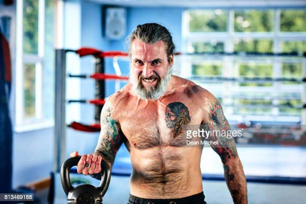 Fit mature man exercising with kettle bell at the gym