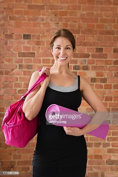 Fit femme d'âge mûr avec tapis de sol et sac de sport