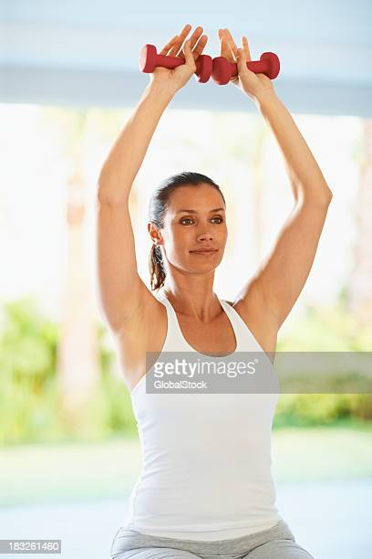 Fit middle aged woman with dumbbells doing exercise