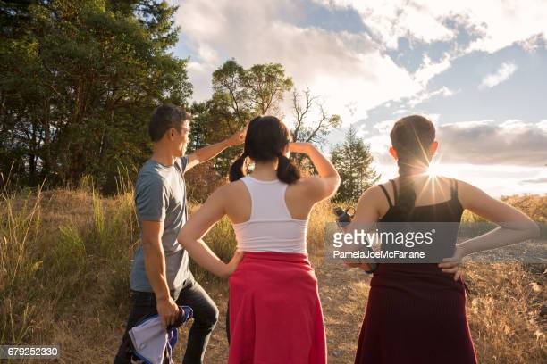 Fit, Multi-Ethnic, Multi-Generation Family of Hikers Walking Towards Sun Light