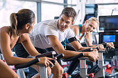 Young people talking and smiling while working out on bike at gym. Friends in a conversation while cycling on stationary bike in fitness centre. Group of happy people working out at exercising class.