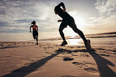 Rear view of two people sprinting on the beach. Man and woman doing running training on the shore in morning.