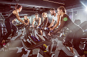 Fit people working out at spinning class in the gym.