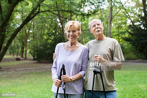 Fit senior couple with walking sticks in the park