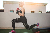 Fit sportswoman exercising with kettle bell on fitness stepper outdoors.