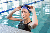 Fit swimmer in the pool smiling at camera at the leisure center