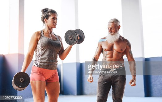 Fit woman doing curl biceps exercise with dumbbells in fitness gym center - Female athlete training with her personal trainer inside wellness sport club - Workout and sportive motivation concept : Stock Photo