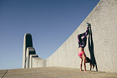 Physically fit woman doing hand stand outdoors. Healthy female standing on hands with feet lifted up against a wall.