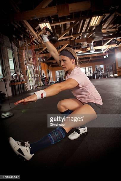 Fit woman doing one legged squats.