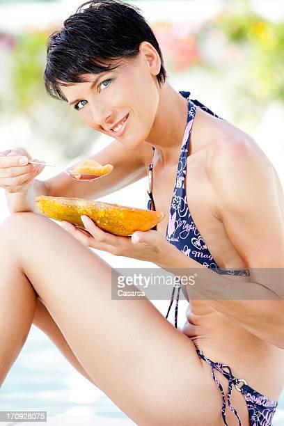 Fit woman eating papaya