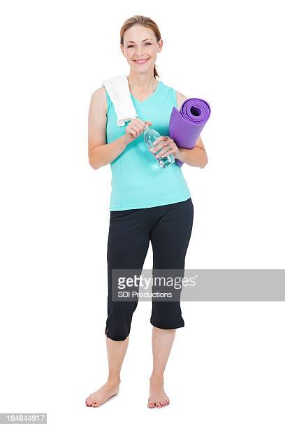 Fit Woman Holding Yoga Mat, Towel, and water bottle