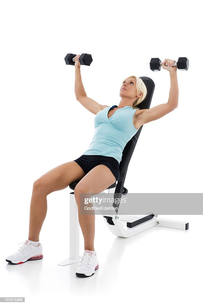 Fit woman lifting weights on weight bench : Stock Photo