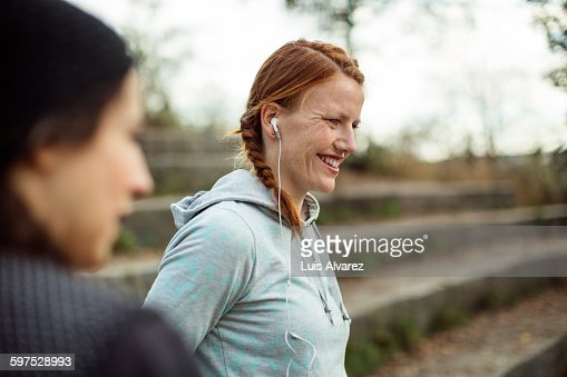 Fit woman listening music at stairway