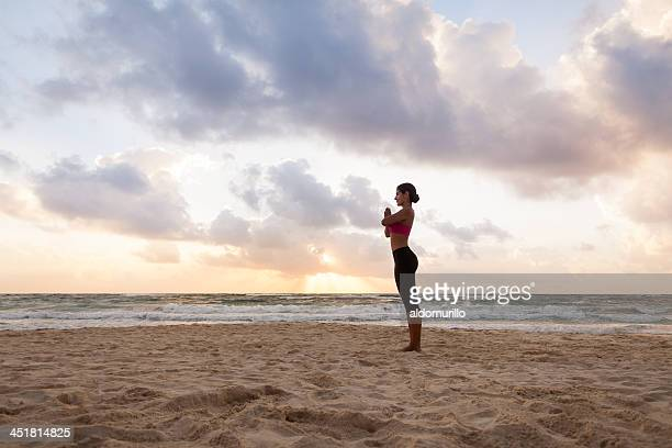 Fit woman practicing yoga at the beach