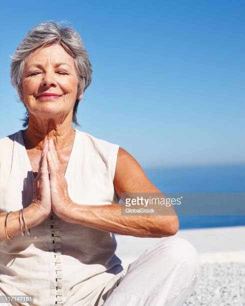 Fit woman practicing yoga with blue sky in the background