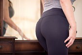 Beautiful Asian woman is ready to go to the gym and she's in her bedroom, standing in front of a vintage vanity mirror. The focus is the model's rear end.