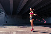 Fit athletic woman runner doing her warming up routine exercises with jumping rope outdoors
